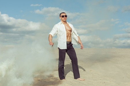 Male bodybuilder standing in the desert, he is holding a cigar. Stock Photo