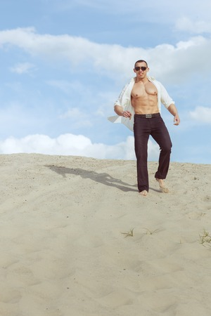 Young macho man with glasses and a cigar in his hand walking through the desert. Stock Photo