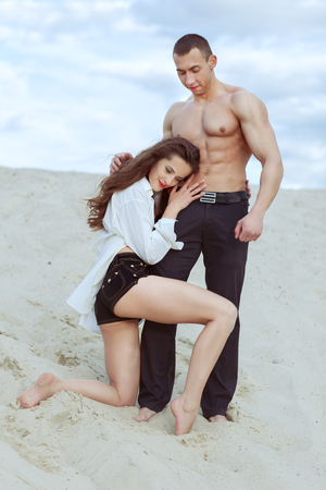 Beautiful pair of lovers in the desert. A girl stands on one knee and hugs a man by the waist.