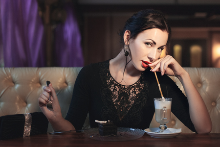 Woman drinks coffee through a pipe and eats a cake, she is in a cafe.