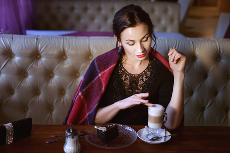Woman at a table in a cafe finger touches the foam on the coffee, she flirts.