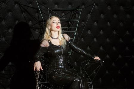 Donna in un vestito di lattice seduta su un trono, lei è la signora BDSM.