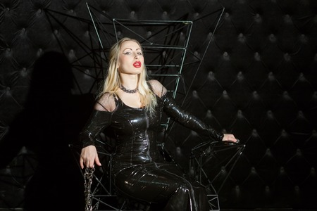 Femme en robe de latex assise sur un trône, c'est Mme BDSM.