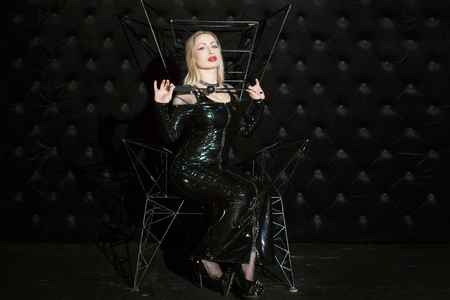 Woman is a mistress, in her hands a gag for the mouth. She is wearing a latex suit for playing humiliation and submission.