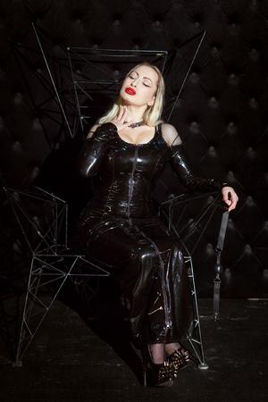 Amante de la mujer erótica en traje de látex para el juego de la sumisión. Foto de archivo