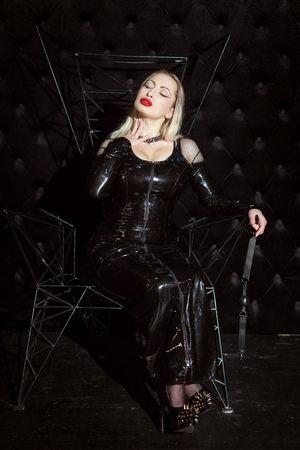 Erotic woman mistress in latex suit for the game of submission.
