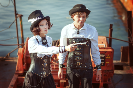 Young couple in the style of steampunk, the woman has a gun in her hand. Stock fotó