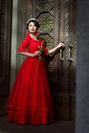 Prinzessin auf dem Hintergrund der Türen zum Schloss, in der Hand eine rote Rose.