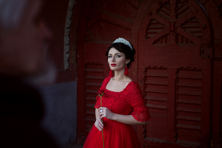 Sad princess with a rose, she is in a red dress and with a diadem on her head. Stock Photo