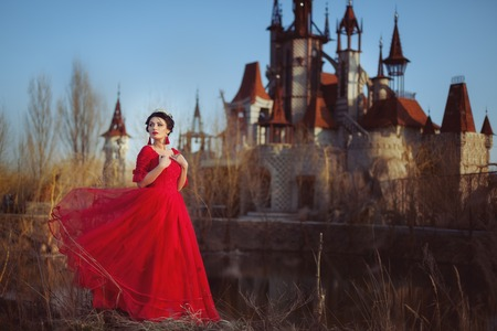 Princess in a red dress on the background of an ancient castle.