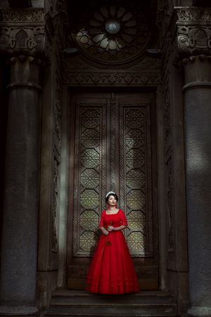 Princess in a red dress stands in the palace against the backdrop of large doors. Фото со стока