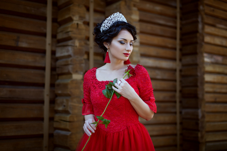 Princess in a red dress, in her hands a rose flower. Фото со стока