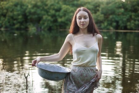 Portrait of a beautiful young laundress in a lake. In her hands she holds a basin. Foto de archivo