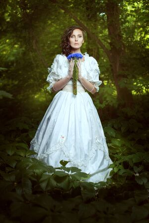Fantastic girl in a white dress with flowers cornflowers in the woods. Dress in retro style. The girl is mysterious and mystical.
