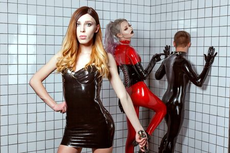 Woman and a man in latex clothes play an adult BDSM game. A woman mocks a man, she humiliates a man. Woman dominates a man. Standard-Bild