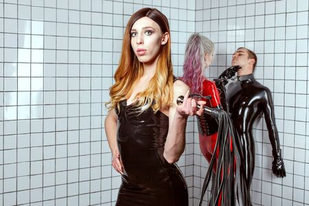 Woman in latex dress with a whip in her hands. She plays an adult game with a man. A woman humiliates a man. Woman dominates a man.