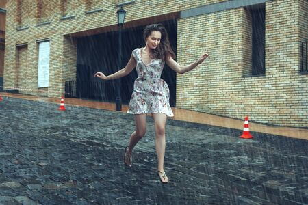 Beautiful young woman runs on the road in the summer rain. Stok Fotoğraf