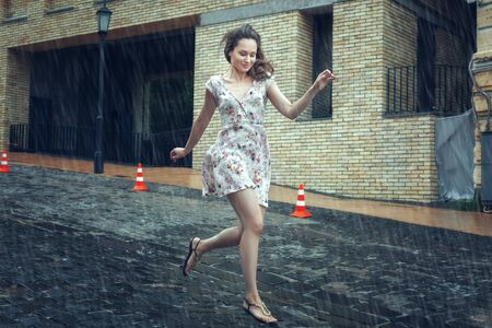 Young woman in a dress runs along the road in the summer rain.