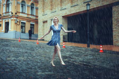 Beautiful blonde woman runs barefoot on the road in the rain.