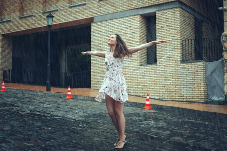 Young woman stands in the rain, she spread her arms and looks up.