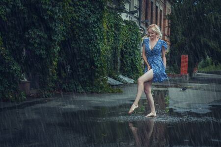 Young blonde woman in a dress frolics through puddles in the summer rain.