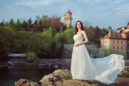 Beautiful young woman in a white dress stands on the banks of the river.