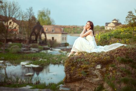 Portrait of a beautiful young woman by the river. She looks thoughtfully into the distance..