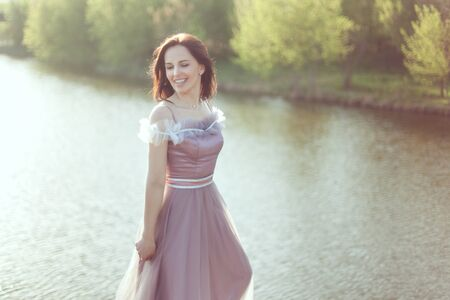 Woman in a purple dress is smiling, she is against the background of nature.