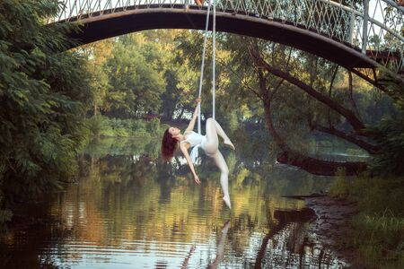 Portrait of acrobat girl on canvases over the river. She does acrobatic stunts.