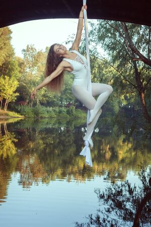 Portrait of a beautiful young acrobat on canvases over a river.