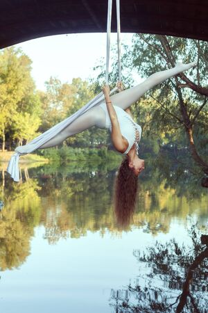 Portrait of a beautiful acrobat on canvases over the river. She does the splits. 스톡 콘텐츠