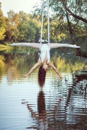 Young girl acrobat hangs on canvases upside down over the river and does the twine.