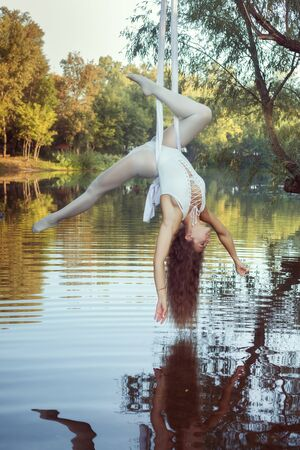 Young acrobat girl does tricks on canvases over the river.