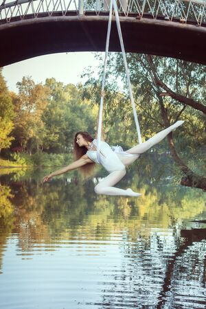 Acrobat girl in a white suit does tricks on canvases over the river. 스톡 콘텐츠