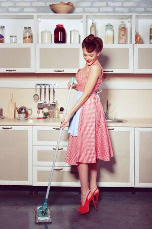 Kobieta w kuchni myje podłogi. Gospodyni sprząta w kuchni.