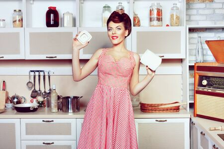 La giovane bella donna sta cucinando nella cucina. Stile pin up..