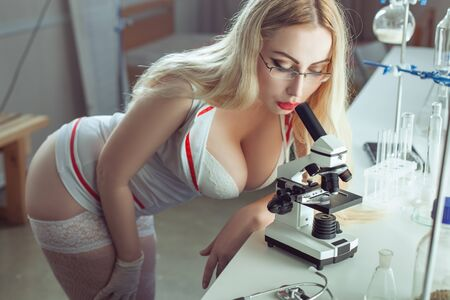 Beautiful sexy nurse in a laboratory looking through a microscope.