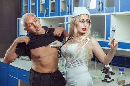 Beautiful sexy nurse listens to a man sheart with a stethoscope and holds a large syringe in his other hand.