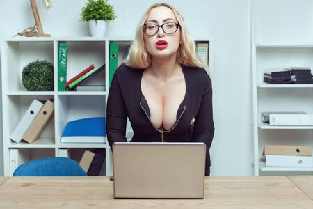 Young woman secretary sits at a table in the office. She works behind a laptop and looks in front of her with a languid look.