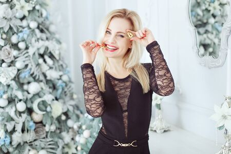 Young beautiful blonde stands near a Christmas tree and holds Bitcoin coins in her hands. She bit one coin with her teeth. Stok Fotoğraf