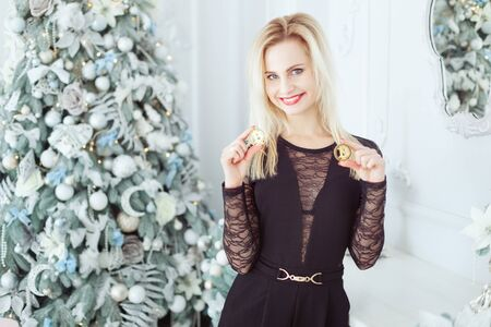 Cute blonde woman stands near a New Year tree and holds Bitcoin coins in her hands.