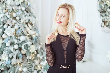 Cute blonde woman near a Christmas tree holds Bitcoins in her hands and laughs.