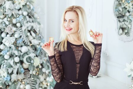 Portrait of a cute blonde woman with bitcoins near a Christmas tree.