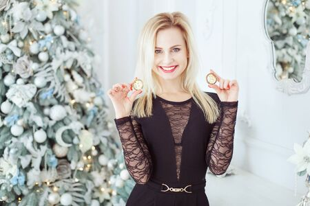 Portrait of a cute blonde woman with bitcoins in hands near a Christmas tree. She is laughing. Stok Fotoğraf