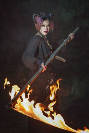 Gloomy female demon mows grass in the darkness with a burning scythe. 写真素材