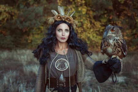 Portrait of a shaman woman in the forest. She has an eagle owl in her hand.