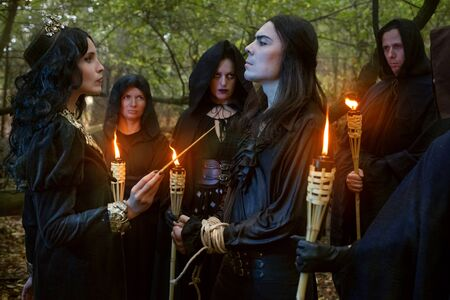 Evil sorceress conducts a magic ritual over a man in the forest.