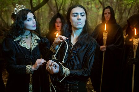 Young woman witch is tying hands to a man. Around them are people in black with torches.