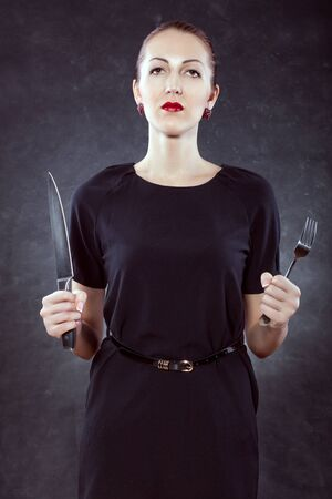 Portrait of a beautiful young woman on a black background with a knife and a fork in her hands.