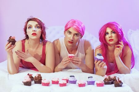 Portrait of beautiful woman dolls and man dolls. They are lying on the couch and eating cakes. Stock fotó